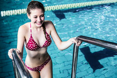 Smiling woman getting out the pool Stock Images