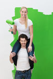 Smiling woman getting a piggy back as she paints Stock Photography