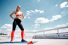 Smiling woman is getting ready for exercising on rooftop stock image