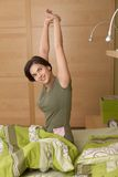 Smiling woman getting up stretching Stock Photo