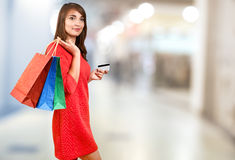 Smiling woman with a gift bag and a credit card Stock Images