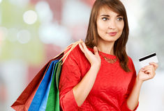 Smiling woman with a gift bag and a credit card Stock Photos