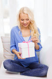 Smiling woman with gift box at home Royalty Free Stock Photography