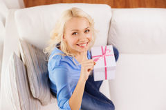 Smiling woman with gift box at home. Holiday, celebration, home and birthday concept - smiling young woman with gift box and making shh gesture at home stock images