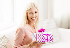 Smiling woman with gift box at home Royalty Free Stock Photos