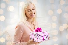 Smiling woman with gift box over holidays lights Royalty Free Stock Photos