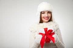 Smiling woman with gift box over light background Royalty Free Stock Photo