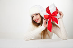 Smiling woman with gift box over light background Stock Photo