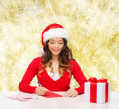Smiling woman with gift box writing letter Stock Photography