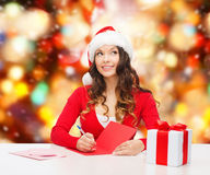 Smiling woman with gift box writing letter Royalty Free Stock Photos