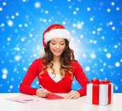 Smiling woman with gift box writing letter Stock Photo