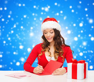Smiling woman with gift box writing letter Stock Photos
