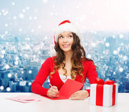 Smiling woman with gift box writing letter Royalty Free Stock Photo