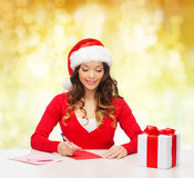 Smiling woman with gift box writing letter Stock Images