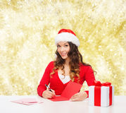Smiling woman with gift box writing letter Royalty Free Stock Image