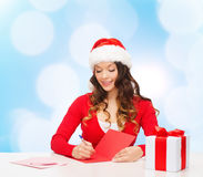 Smiling woman with gift box writing letter Stock Image