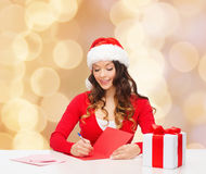 Smiling woman with gift box writing letter Royalty Free Stock Images