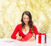 Smiling woman with gift box writing letter Royalty Free Stock Photography