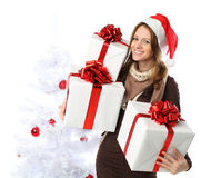 Smiling woman with gift and Christmas tree Royalty Free Stock Image