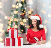 Smiling woman with gifts, laptop and credit card Royalty Free Stock Photo