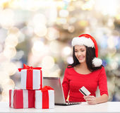 Smiling woman with gifts, laptop and credit card Royalty Free Stock Photos