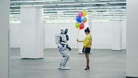 Smiling woman gifts many balloons to one droid, standing in a room. stock footage