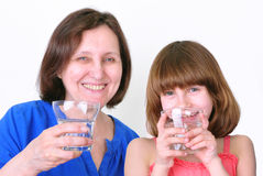 Smiling woman and girl drink water Royalty Free Stock Images
