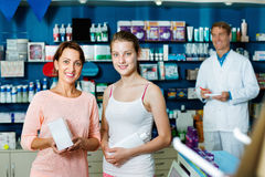Smiling woman with girl teenager packing body care goods. Smiling cheerful women with girl teenager packing body care goods in pharmaceutical store Stock Images
