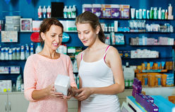 Smiling woman with girl teenager packing body care goods royalty free stock image