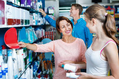 Smiling woman with girl teenager packing body care goods Royalty Free Stock Photo