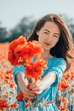 Smiling woman giving a bouquet of poppies. Smiling beautiful brunette young woman giving a bouquet of poppies in flower meadow outdoor royalty free stock photo