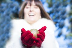 Smiling woman giving christmas tree ball wearing red gloves Stock Images