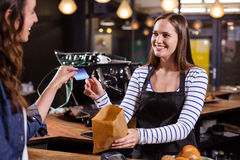 Smiling woman giving credit card to barista Royalty Free Stock Photography