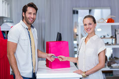 Smiling woman giving credit card to cashier. Portrait of smiling women giving credit card to cashier in clothing store Stock Photo