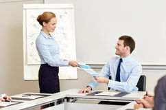 Smiling woman giving papers to man in office Stock Image