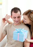 Smiling woman giving a present to her boyfriend Royalty Free Stock Images