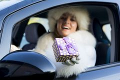 Smiling woman giving a purple gift box wearing red gloves Stock Photos