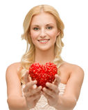 Smiling woman giving small red heart Royalty Free Stock Images