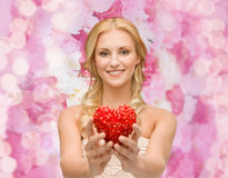 Smiling woman giving small red heart Royalty Free Stock Photos
