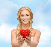 Smiling woman giving small red heart Royalty Free Stock Image