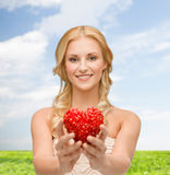 Smiling woman giving small red heart Stock Image