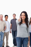 Smiling woman giving thumb up with friends behind her Royalty Free Stock Image