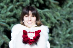 Smiling woman giving a white gift box with red dots wearing red Stock Photos