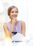 Smiling woman with glass of whine waiting for date Stock Photo