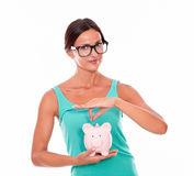 Smiling woman with glasses holding pink piggy bank Royalty Free Stock Image