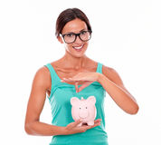 Smiling woman with glasses holding pink piggy bank Royalty Free Stock Images