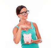 Smiling woman with glasses holding pink piggy bank. In one hand and gesturing saving money with the other hand, wearing a tank top isolated Stock Images
