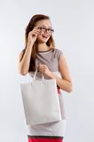 Smiling woman in glasses holding shopping white bag Stock Photos