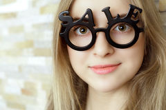 Smiling woman with glasses shaped into SALE text Stock Photo