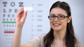 Smiling woman in glasses showing contact lens case, recommending new technology. Stock footage stock video footage